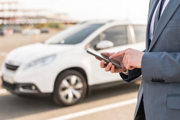 車の前にスマートフォンを持つビジネスマン