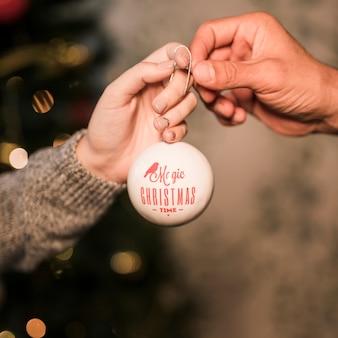 飾りつけのクリスマスボールを男に与える女性