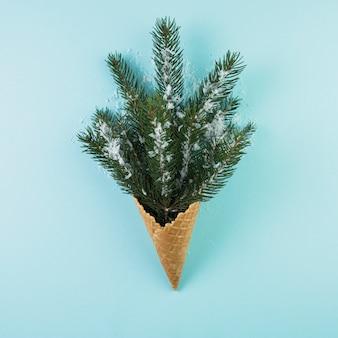 モミの枝と飾りの雪の入ったウエハーカップ