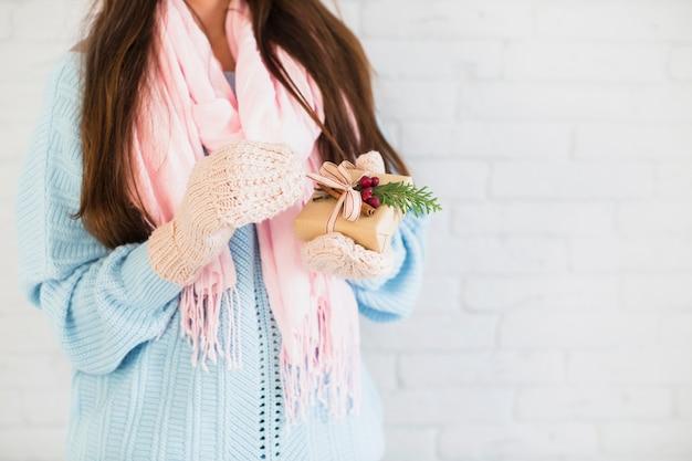 ミトン、手でギフトボックスとスカーフのブルネットの女性