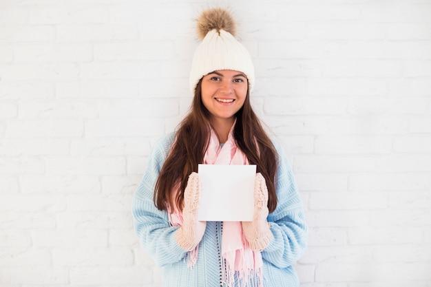 ミトン、帽子、スカーフ、正方形の紙で朗らかな女性