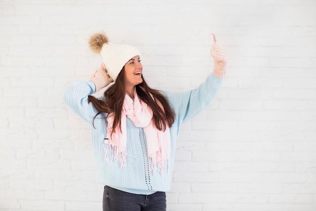 スマートフォンでセルフをするミトン、かわいい帽子、スカーフの陽気な女性