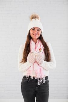 ミトンの魅力的な女性、マグカップとキャンディー付きのボブル帽子、スカーフ