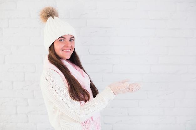ミトンの魅力的な女性、開かれた手でのボウルの帽子、スカーフ