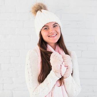 ミトン、かわいい帽子、スカーフで魅力的な女性を笑顔