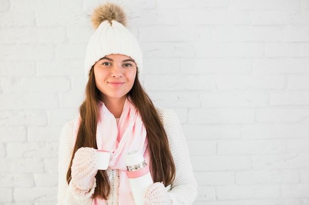 ミトンの魅力的な女性、泡立つ帽子、魔法瓶付きのスカーフ