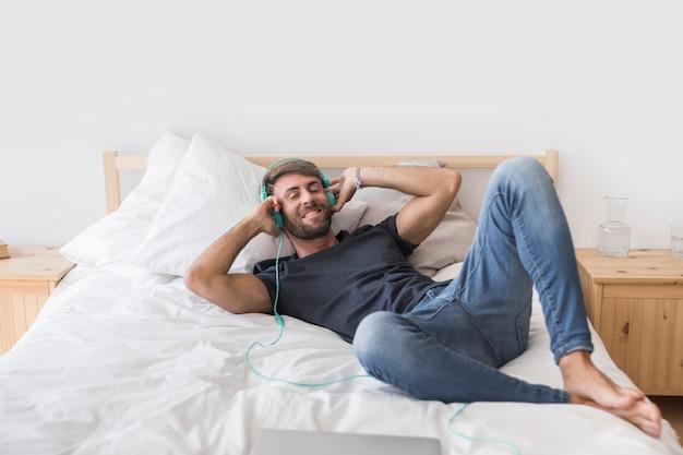 幸せな若い男がベッドで音楽を聴く