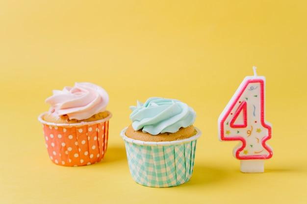 キャンドルの隣に誕生日カップケーキ