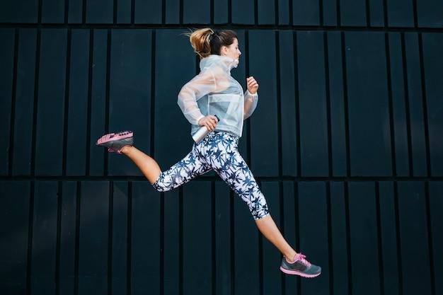 都市環境で走っているスポーティな女性