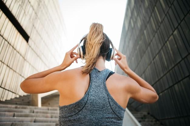 都市環境でヘッドフォンを持つスポーティーな女性