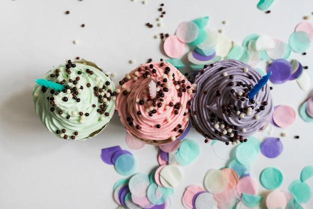 色とりどりのチョコレートボールが付いているトップのパステルカラーのカップケーキ