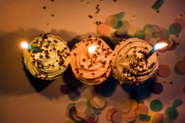 トップの蝋燭とチョコレートボールとパステルカラーのカップケーキ