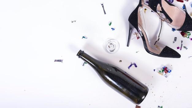 Женские черные каблуки лежат возле бутылки после вечеринки