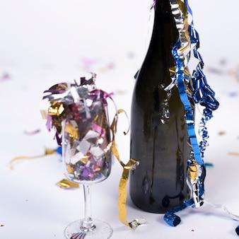 Темная бутылка и стакан, наполненный конфетти