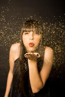 手から紙吹雪を吹く若い女性