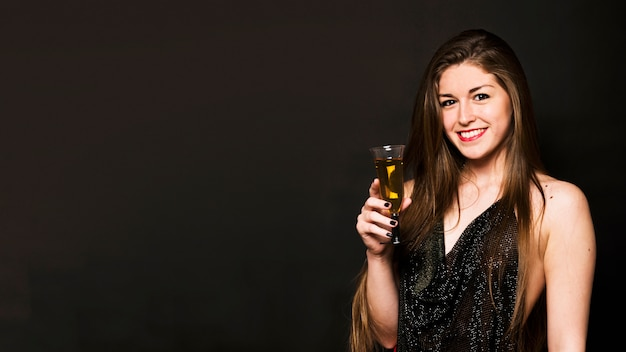 ドリンクのガラスと夕方の布の魅力的な幸せな女性