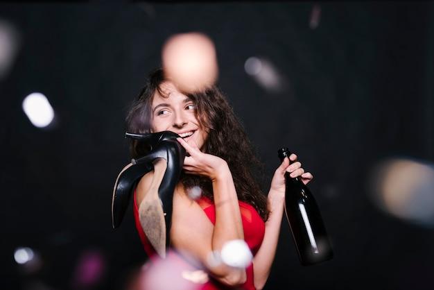 Счастливый женщина, стоя с бутылкой на вечеринке