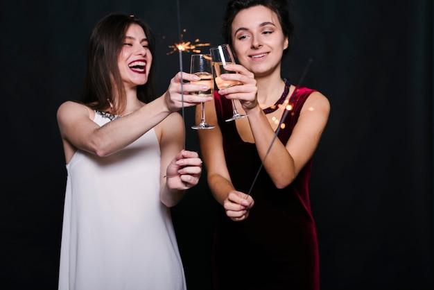 女性はシャンパンのメガネをつまむ