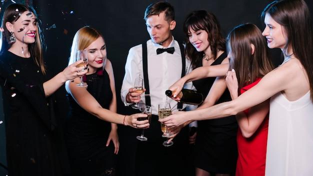 パーティーでシャンパンのメガネを握っている人々