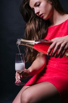 Женщина, наливая шампанское в стекло