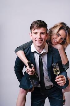 シャンパンを持つ男の背中に座っている女性