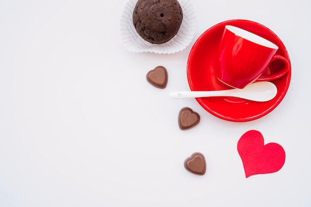 Чашка на тарелке рядом с шоколадными конфетами, булочкой и валентинкой