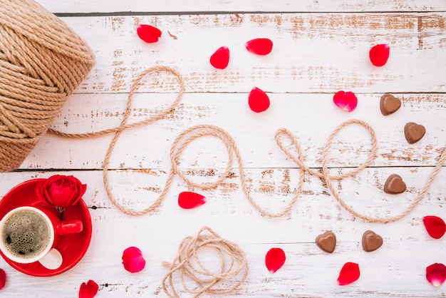 Любовь название нитки возле чашки напитка на тарелке, шоколадные конфеты и лепестки