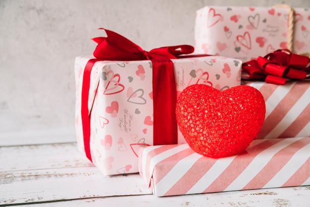 Декоративное сердце возле кучи подарочных коробок в обертке