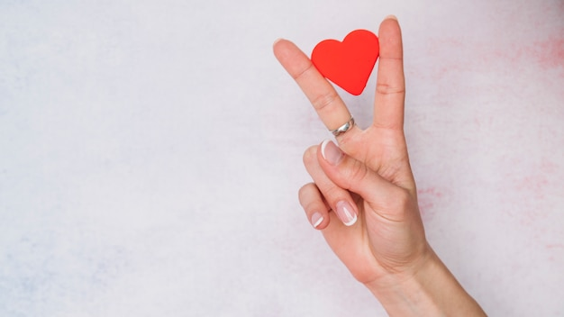 指の間に紙の心を持つ女性の手