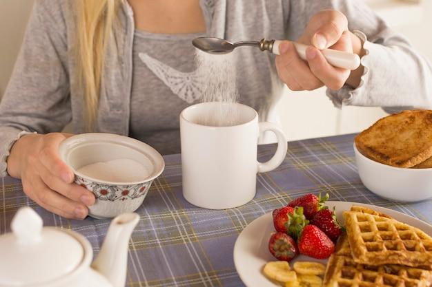 Девушка добавляет сахар в чай