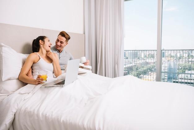 朝のベッドで抱きしめて笑うカップル