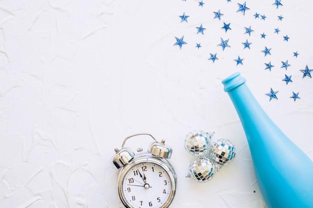 白いテーブルに時計とスパンコール付きのボトル