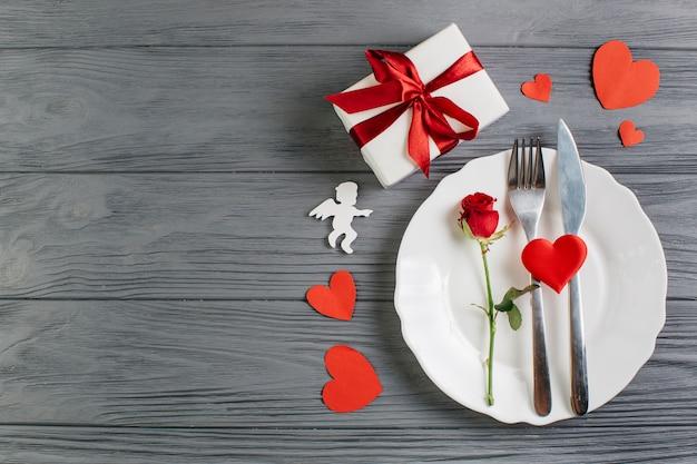 Красная роза с столовыми приборами на белой тарелке