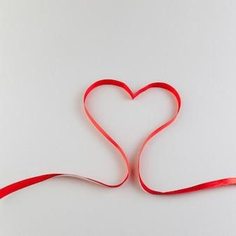 赤いサテンのリボンで作られた心