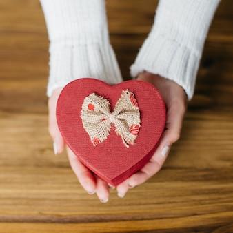 Руки с подарочной коробкой в форме сердца