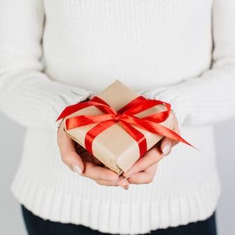 優しく赤いリボンでプレゼントをしている女性