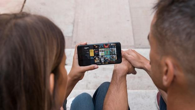 アマゾンプライムビデオアプリを表示するスマートフォンのカップル