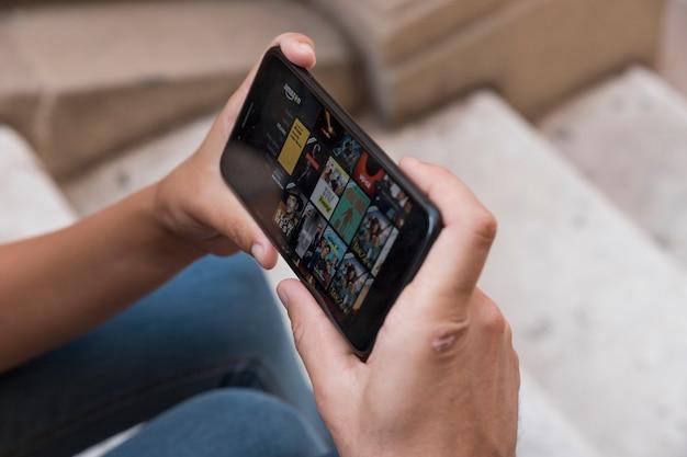 アマゾンプライムビデオアプリを示すスマートフォンを手にして