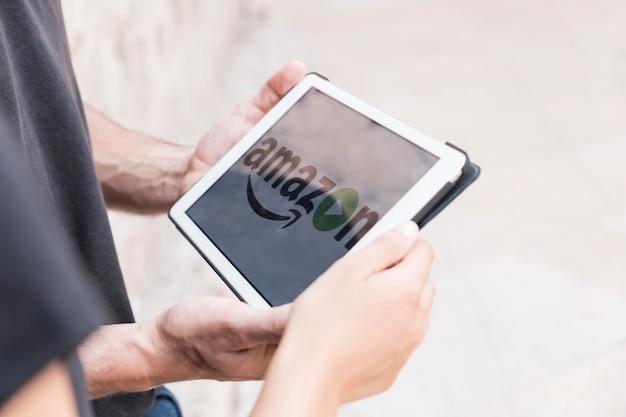 アマゾンプライムビデオアプリを表示しているタブレットを持つ男