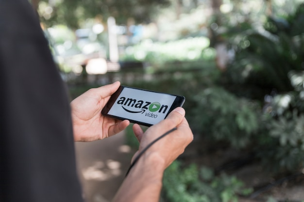 アマゾンプライムビデオアプリを見せるスマートフォンを持つ男