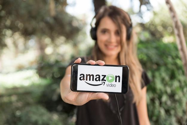 アマゾンプライムビデオアプリを表示しているスマートフォンを持つ女性