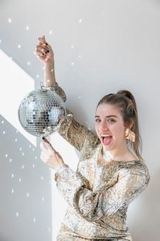 ディスコボールを持っている女の子と新年のパーティーのコンセプト