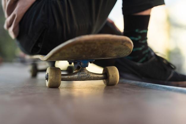 スケートボードに座っている若い男