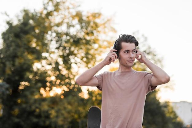 スケートボードとイヤホンでポーズを取る若い男