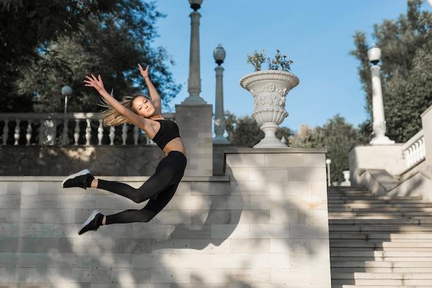 ジャンプする若いスポーティーな女性