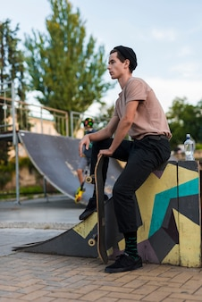 スケートボードでポーズを取る若い男