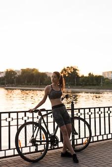 自転車でポーズを取るスポーティな若い女性
