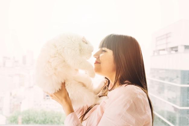 彼女の猫とポーズをとっている幸せな少女