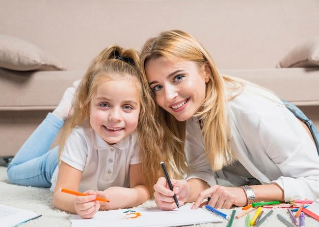 母親と娘が床に絵を描く