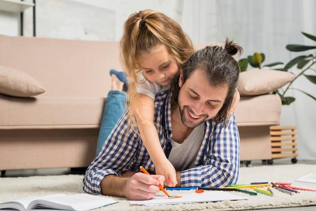 父と娘が床に絵を描く